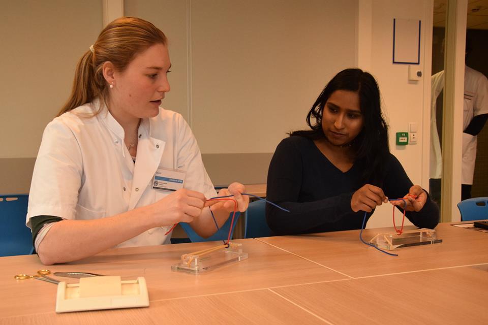 Een student doet stap voor stap voor aan een scholier hoe je chirurgisch moet knopen