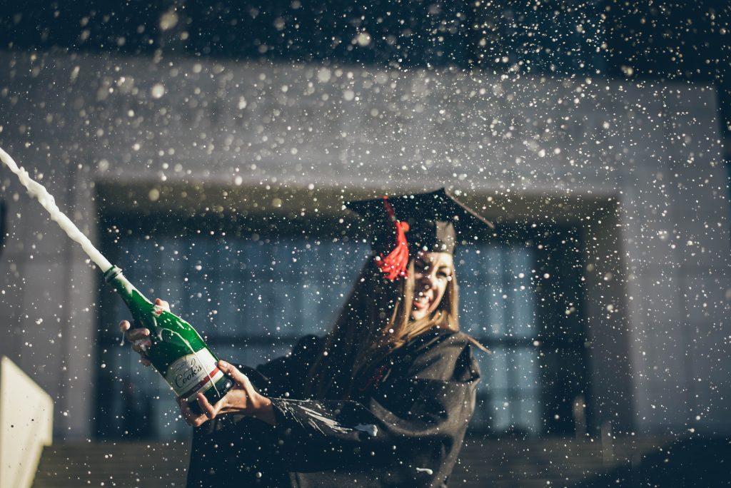 Een student draagt een graduation cap en viert het met champagne