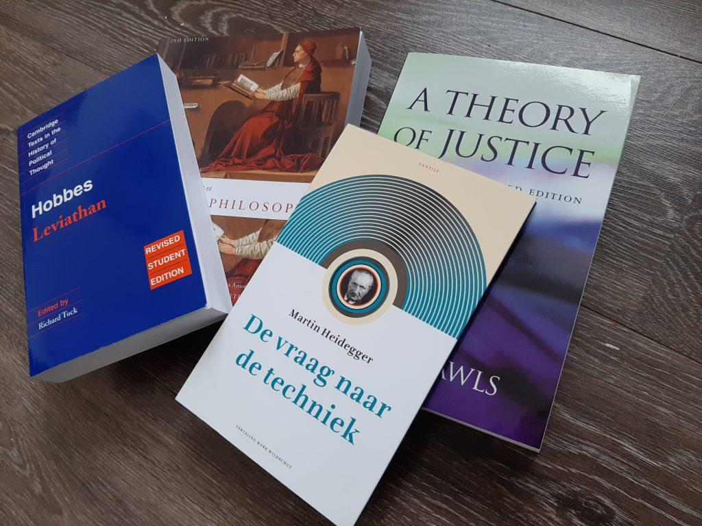 Vier filosofie studieboeken: de Leviathan van Hobbes, verzameld werk van middeleeuwse filosofie, A Theory of Justice van John Rawls en De vraag naar de techniek van Heidegger.