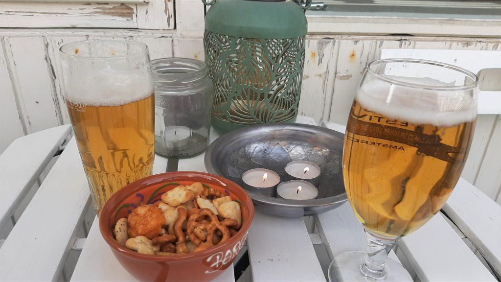 Twee biertjes en een bakje nootjes op een terrasje.