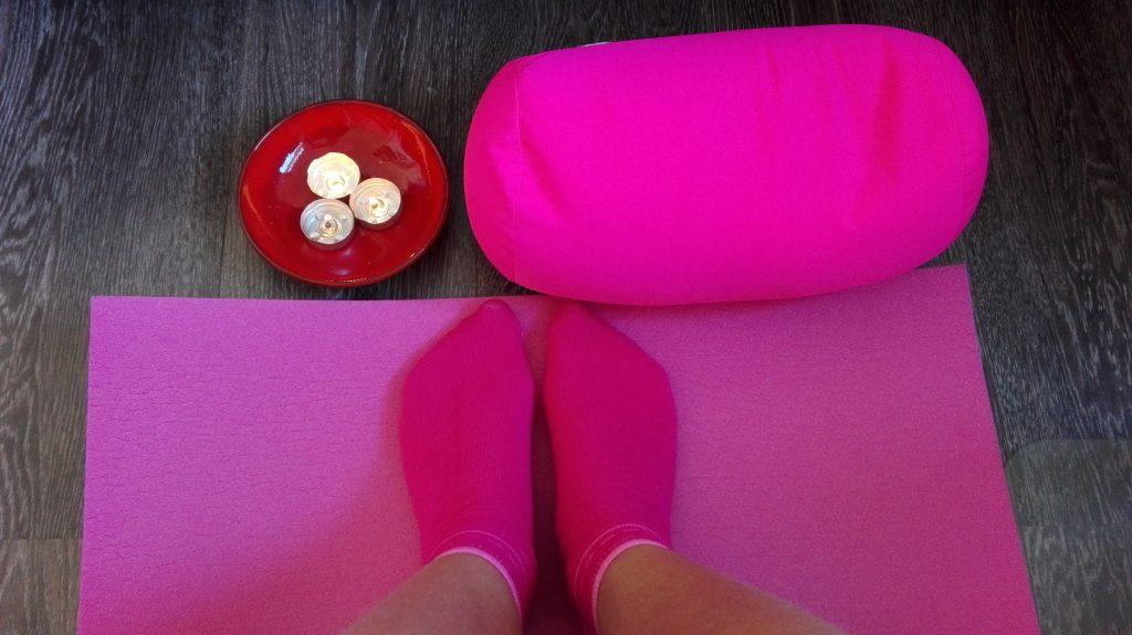 Ik op mijn yoga mat, met een yoga kussen en drie kaarsjes.