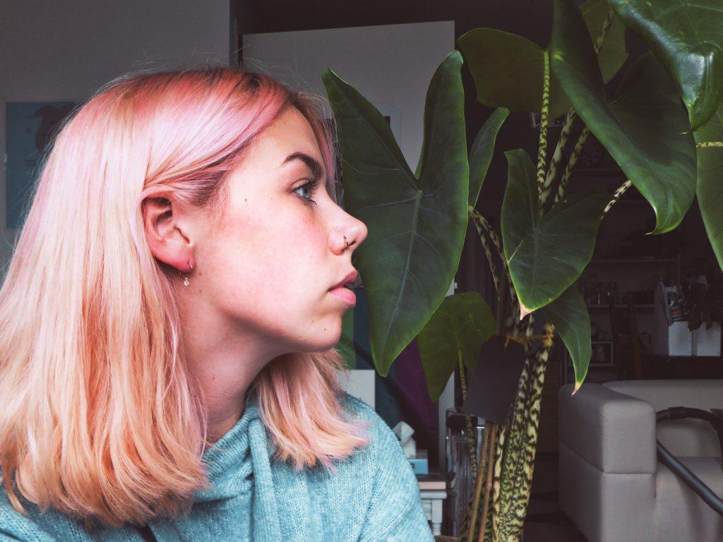 Foto van het kapsel behaald door studentenkortingen van de auteur: de rechterzijde van een perzikkleurige coupe op schouderlengte. Ze draagt een blauwe trui en zit naast een Alocasiaplant