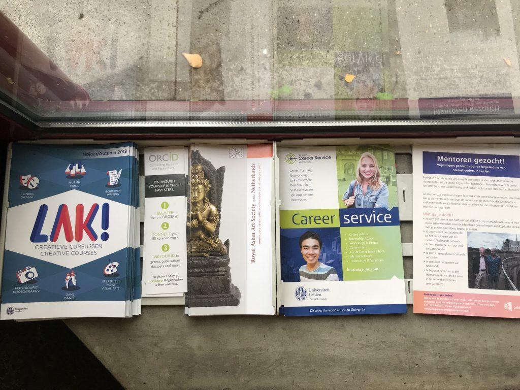Folders in de vensterbank van het huizinga waarop het Leidse aanbod van activiteiten te zien is  zoals creatieve cursussen, careerservice en een vacature voor studentenmentoren.