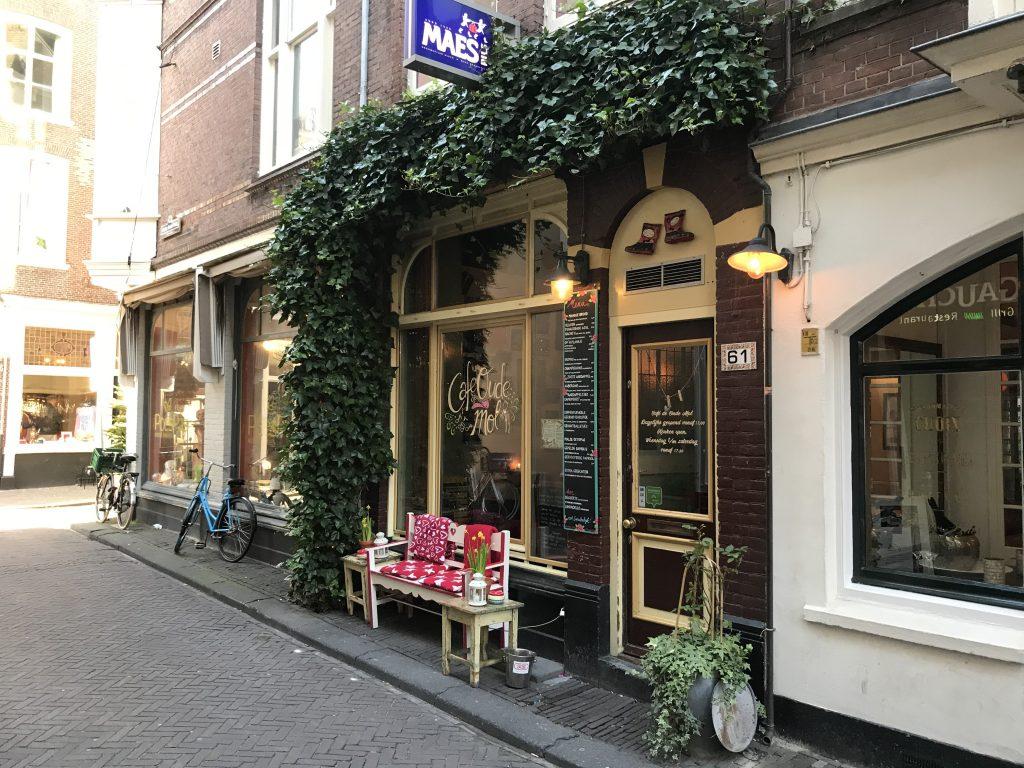 Foto van café de oude mol, een gezellig plekje met groene klimop vboven de deur en gebloemde dekentjes voor de mensen op het terras.
