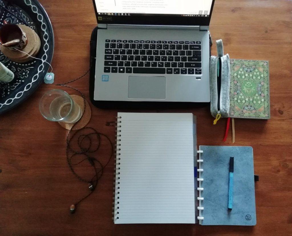 bovenaanzicht van tafel met laptop, schrift en agenda