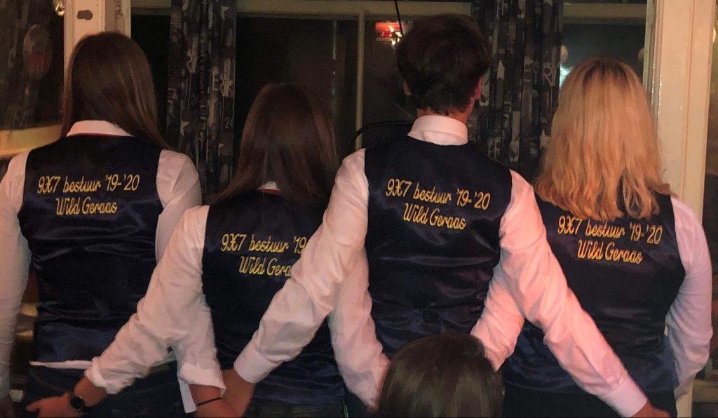 """Vier bestuursleden met de rug naar de camera toegekeerd. Op de achterkant van hun vestje staat """"9X7 bestuur 19-20 Wild Geraas"""""""