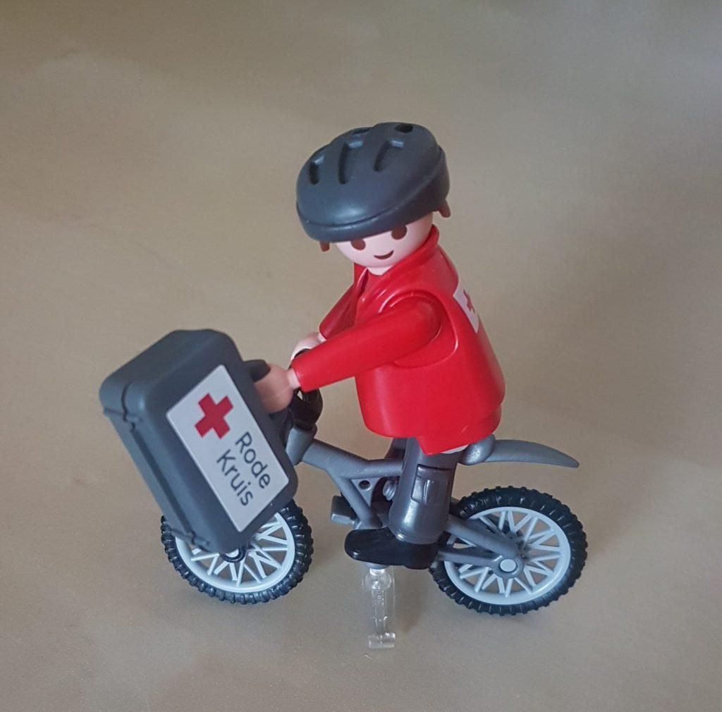 Playmobilpoppetje met rood vest. Hij draagt een helm, zit op een fiets en draagt een grijs koffertje met het Rode Kruis logo.