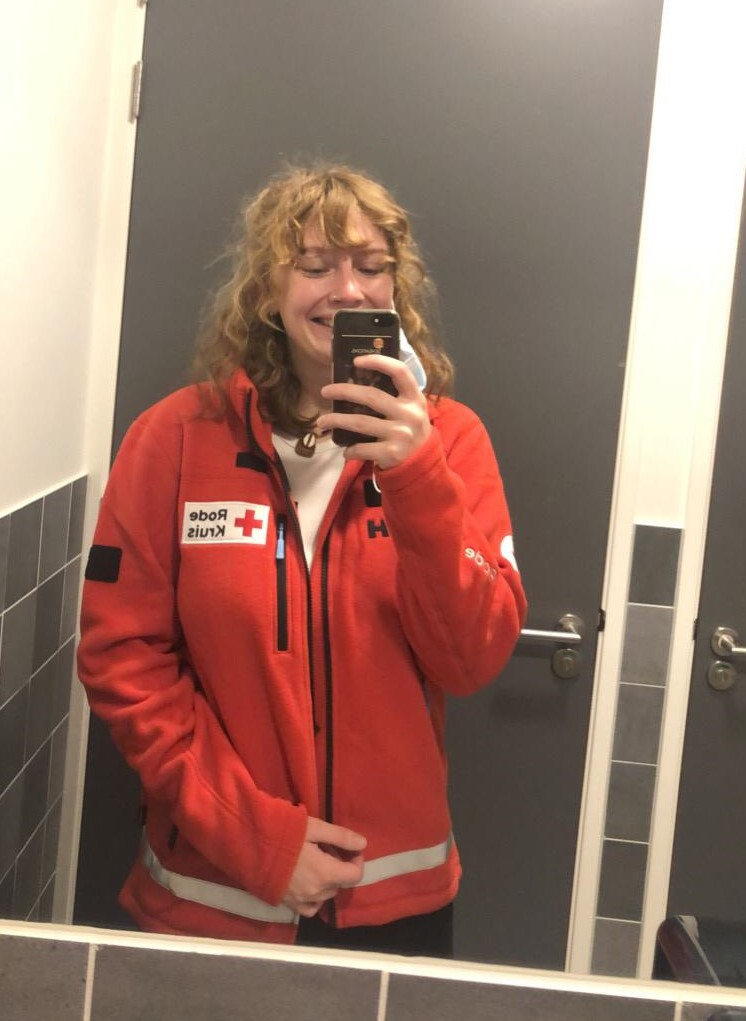 Selfie in een spiegel van verpleegkundestudent Astrid in vest van Rode Kruis