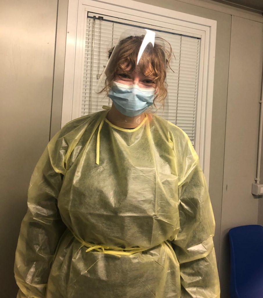 Verpleegkundestudent Astrid draagt een geel schort, een blauw mondkapje en een spatscherm om zichzelf te beschermen
