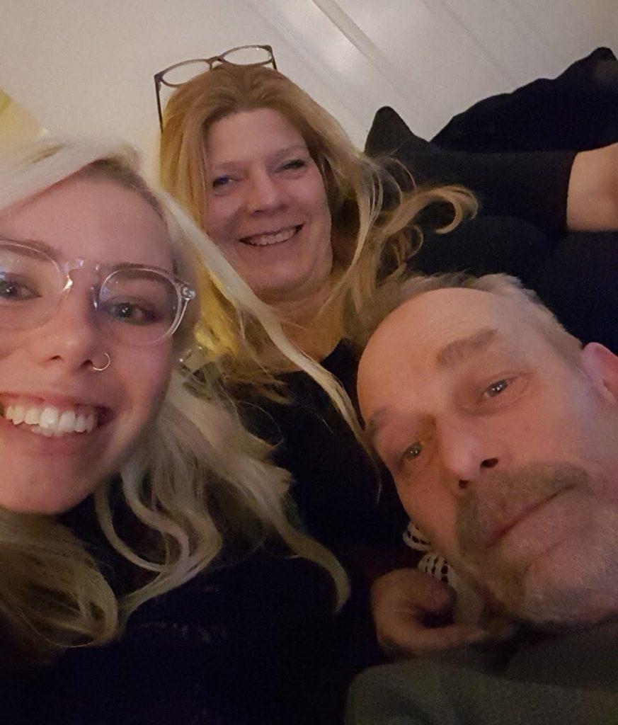 Vader, stiefmoeder en dochter op de bank in het weekend