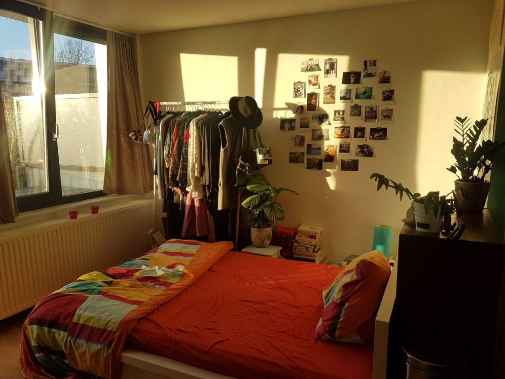 Uitzicht op studentenkamer, bed, kledingrek en foto's aan de muur. Met geluk binnen 3 uur thuis, de weekenden.