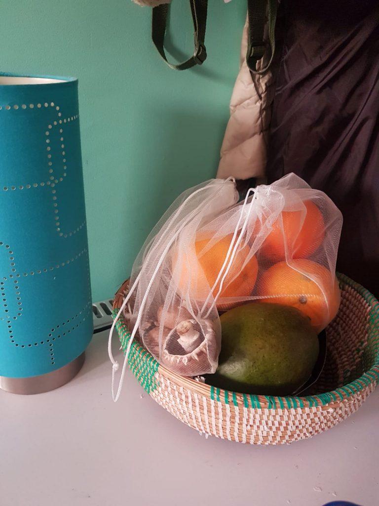 Fruit- en groentemandje gevuld met komkommer, mango, sinaasappels en kastanjechampignons in een netje