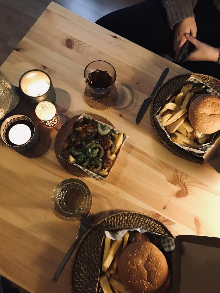 Een tafel met kaarsen, burgers en friet.