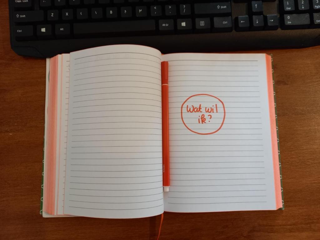 """Foto van een notitieboekje waar met rode stift in geschreven is """"Wat wil ik?"""""""