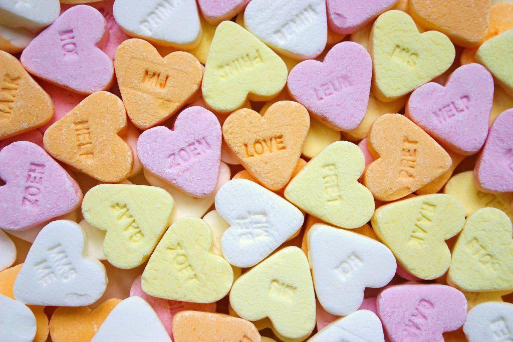 """Een foto van hartjessnoepjes in verschillende kleuren met woorden erop zoals """"Zoen"""" en """"Love"""""""