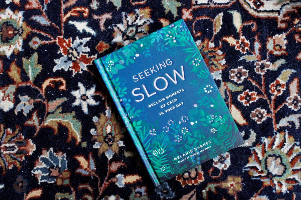 Het boek Seeking Slow van Melanie Barnes met als achtergrond een Perzisch tapijt