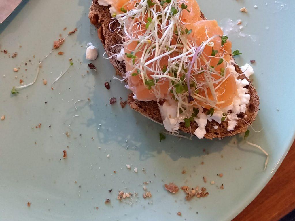 groen bord met daarop een boterham met cottage cheese gerookte zalm en kiemgroenten